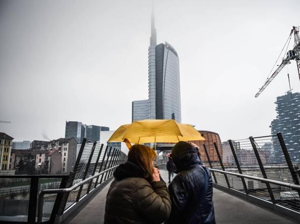 La prima pioggia dell'anno in piazza Gae Aulenti (Fotogramma)