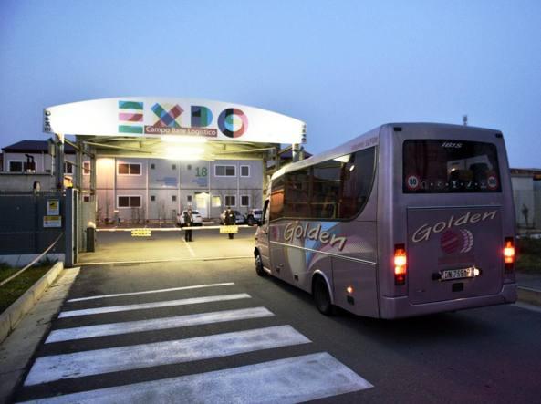 L'arrivo di un pullman con un gruppo di profughi al campo base Expo (Fotogramma)