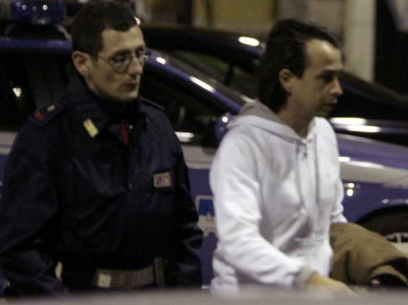 Danilo Coppola con la polizia davanti alla Questura di Roma giovedì dopo l'arrivo in macchina da Milano (Ansa)