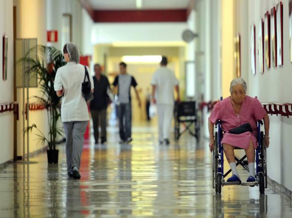 donna anziana in carrozzina in una corsia di ospedale