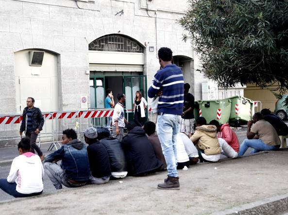 Un gruppo di profughi all'esterno dell'hub di prima accoglienza in via Sammartini (LaPresse)