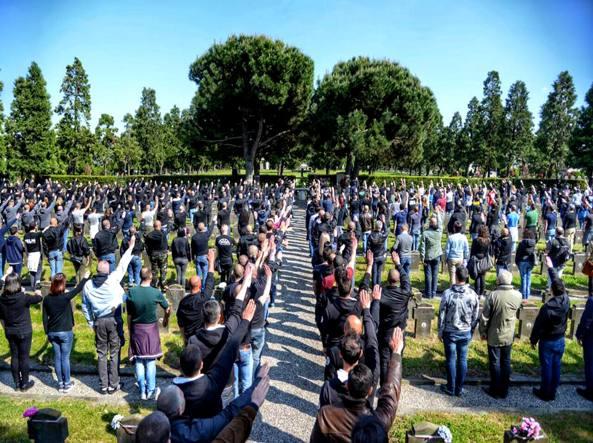 La cerimonia non autorizzata al Cimitero Maggiore: tutti di spalle per non essere riconosciuti (Ansa, foto da Facebook)