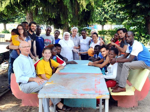 Foto di gruppo alla parrocchia Beata Vergine Assunta di Bruzzano, che in estate ospita migranti (Fotogramma)