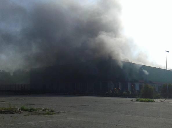 La densa colonna di fumo che si è alzata dal magazzino di Trezzano sul Naviglio visibile anche dalla Tangenziale (foto Vittorio Aggio)